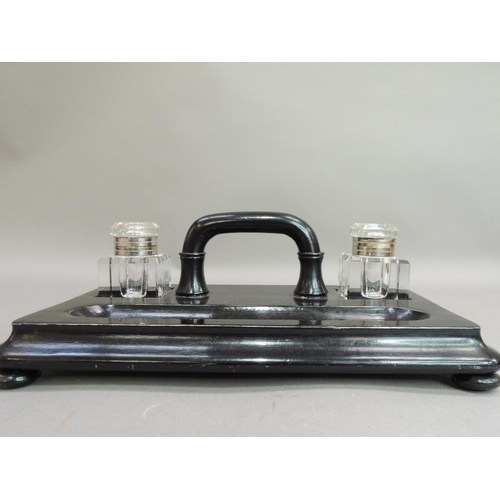 12 - A Victorian ebonised ink stand of rounded rectangular form set with pair of wells, arched handle and...