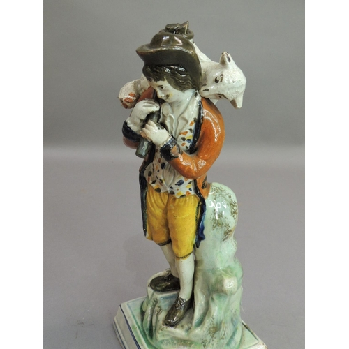 16 - An 18th century Yorkshire pottery figure of a shepherd with sheep over his shoulder, standing before...