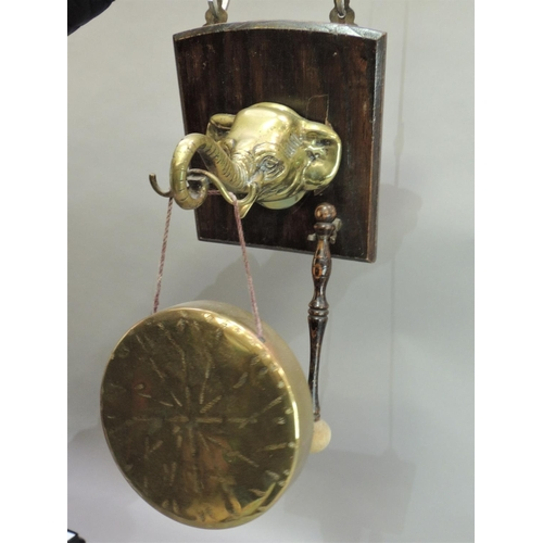 2 - A dinner gong, the oak back plate set with brass elephant head, the gong supported on the trunk, wit...