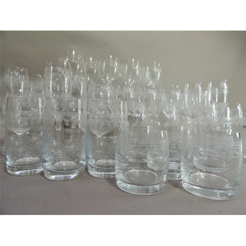 25 - A suite of etched glassware comprising twelve champagne flutes, six brandy glasses, six short and si...