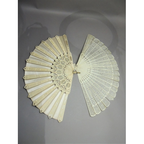 31 - A Cantonese bone fan, pierced sticks, 27cm high in lacquer box together with another fan with pierce...