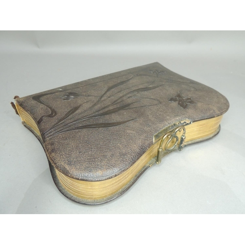 32 - A late Victorian Morocco leather photograph album of rounded rectangular form, the cover embossed wi...