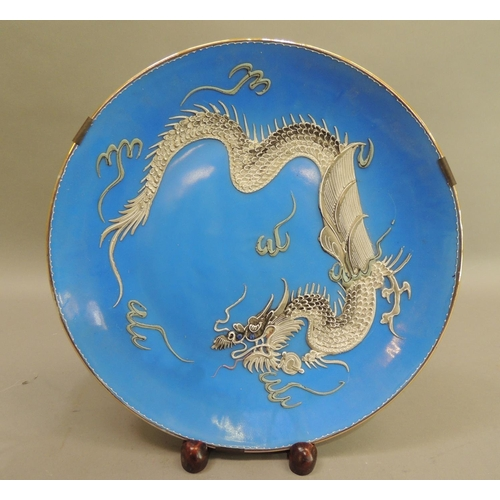 37 - A Nagasaki porcelain plate, heavily enamelled in greys with a dragon on a bright blue ground, 31cm d...