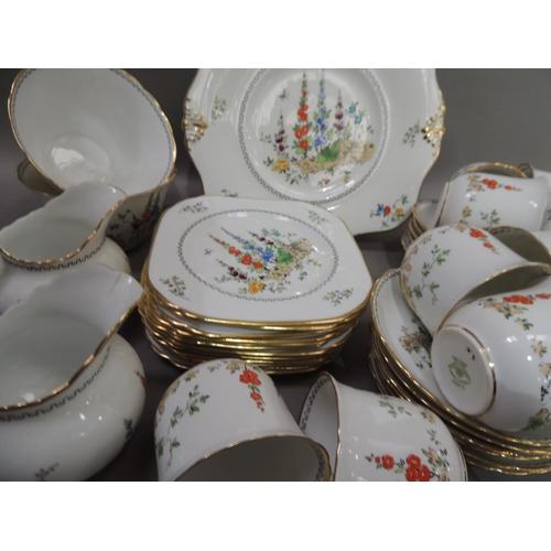 52 - A Tuscan china tea service comprising ten cups, twelve saucers, twelve side plates, two sugar bowls,...