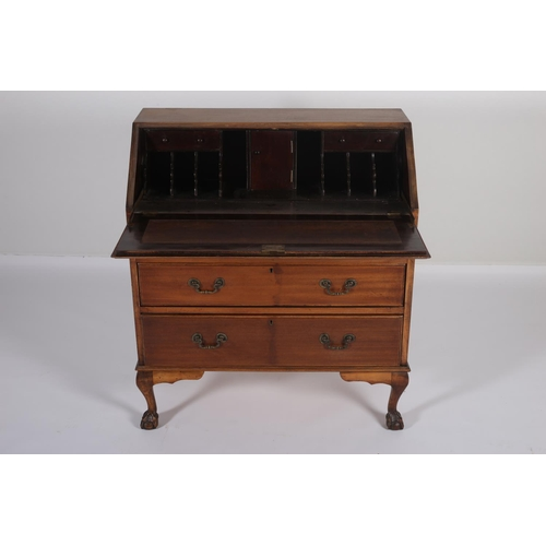 3 - A MAHOGANY BUREAU the hinged writing slope containing pigeon holes and drawers above three long draw...