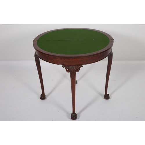 33 - A GEORGIAN DESIGN MAHOGANY FOLD OVER CARD TABLE of demilune outline the shaped top with carved rim a...