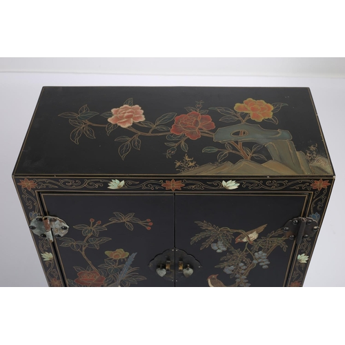 5 - A CHINESE BLACK LAQUERED AND POLYCHROME SIDE CABINET the rectangular top above a pair of panelled do...