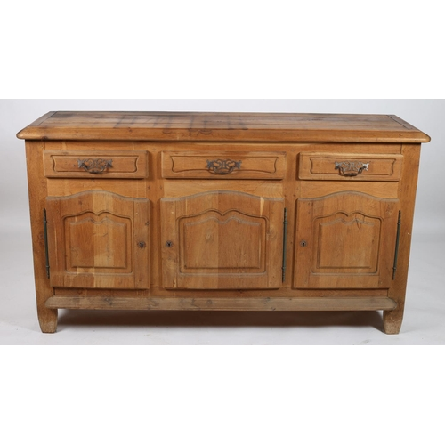 11 - A CONTINENTAL OAK DRESSER of rectangular outline the shaped top above three frieze drawers and cupbo...