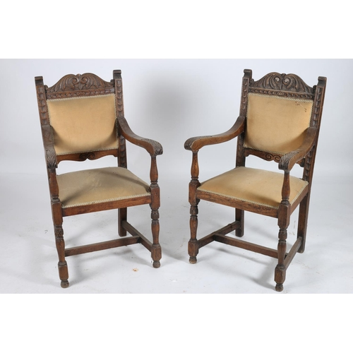 20 - A PAIR OF CONTINENTAL CARVED OAK ELBOW CHAIRS each with a C-scroll and foliate carved top rail with ...