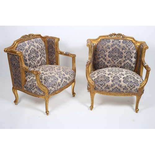 39 - A PAIR OF CARVED GILTWOOD AND UPHOLSTERED ARMCHAIRS each with a carved foliate top rail above an uph...