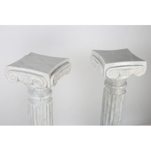 41 - A PAIR OF LIGHT GREY VEINED MARBLE PEDESTALS each with a reeded column and doric capitals above a ci...