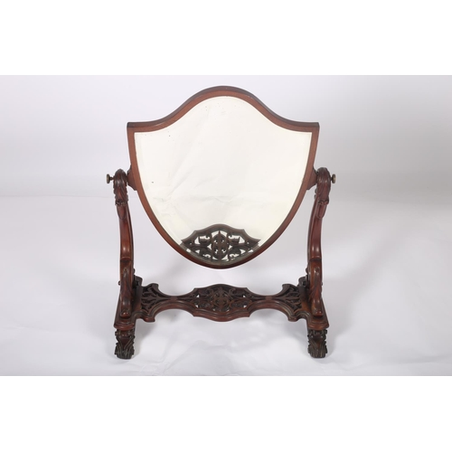 48 - A 19TH CENTURY CARVED MAHOGANY CRUTCH FRAMED MIRROR the shield shaped bevelled glass plate within a ...