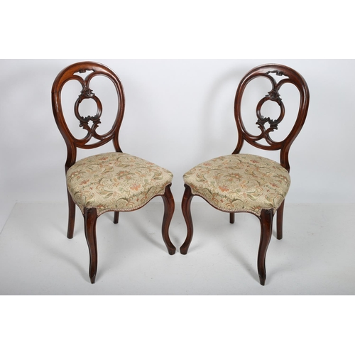 53 - A PAIR OF VICTORIAN MAHOGANY SIDE CHAIRS each with an oval back and pierced carved splat with uphols...