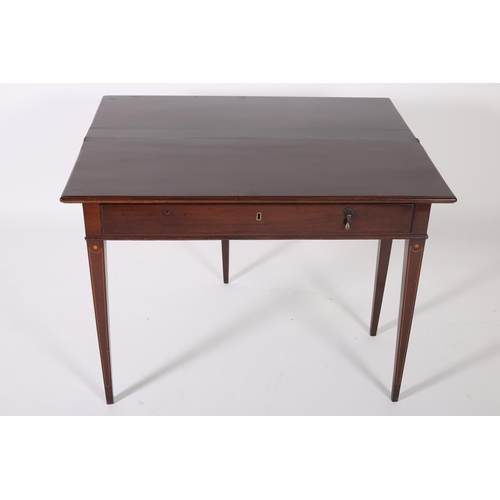 55 - A GEORGIAN MAHOGANY FOLD OVER SUPPER TABLE the rectangular hinged top with frieze drawer on square t...