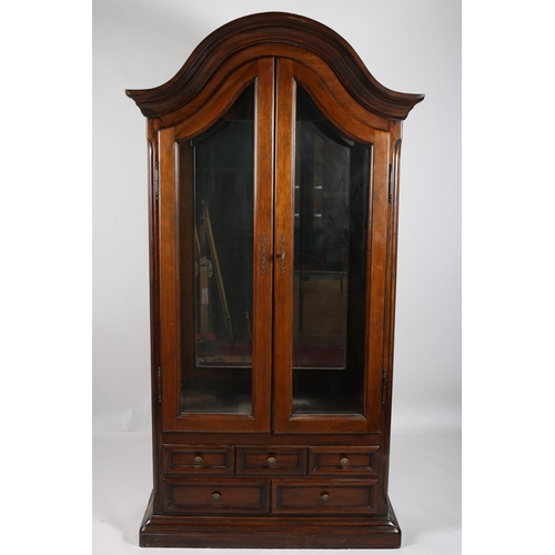 6 - A CONTINENTAL MAHOGANY DISPLAY CABINET the dome shaped hood above a pair of shaped bevelled glazed d...
