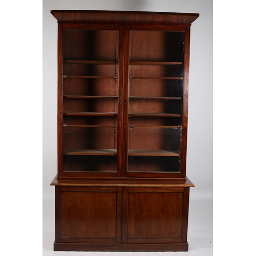 8 - A 19TH CENTURY MAHOGANY TWO DOOR LIBRARY BOOKCASE the moulded cornice above a pair of glazed doors c...