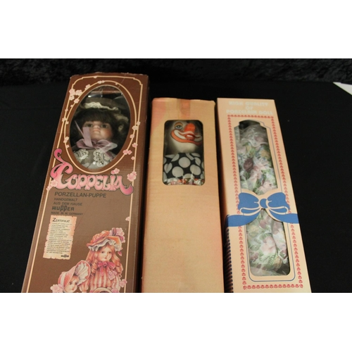 85 - 2 x porcelain boxed dolls with clown...