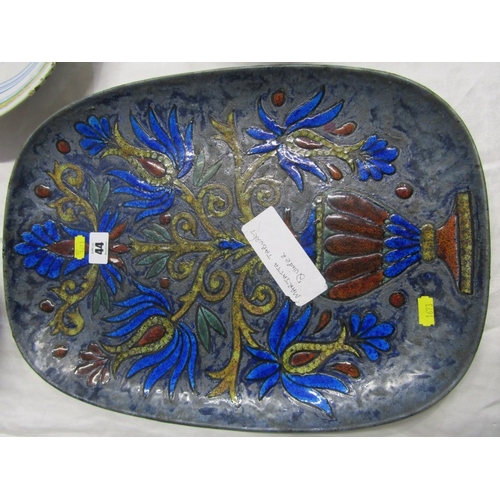 44 - QUIMPER, a signed art pottery enamelled plaque by Marjatta Taburet decorated with stylised vase of f...