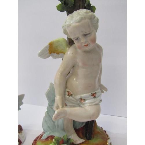 105 - CONTINENTAL PORCELAIN, pair of 19th Century Cupid base candlesticks, underglaze blue crossed scissor...