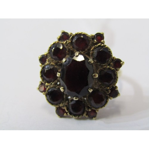 391 - 9CT YELLOW GOLD GARNET CLUSTER RING, principal oval garnet surrounded by graduated size garnets in 9...