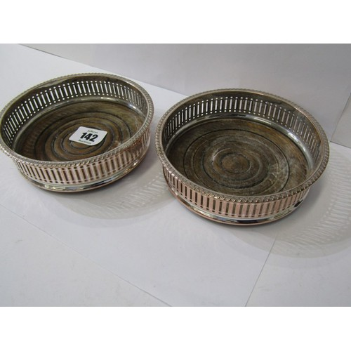 142 - DECANTER COASTERS,  A pair of plated decanter coasters with pierced borders and turned wood bases, 5...