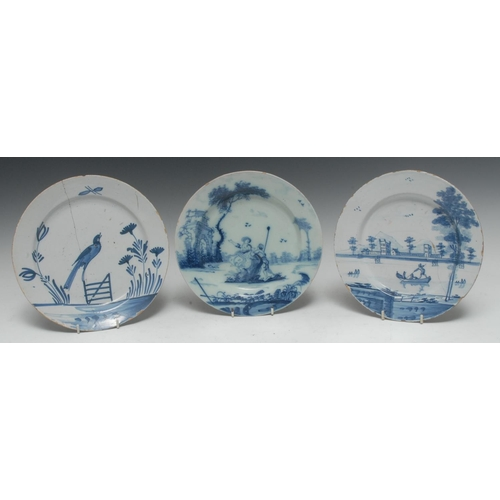 10A - An 18th century Delft circular plate, painted in underglaze blue with figures in an Italianate lands...