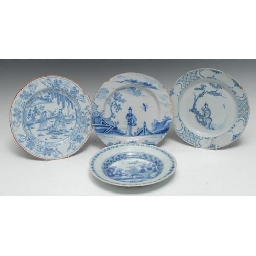 10B - An 18th century Delft circular plate, painted with Chinese figures in a landscape, red line rim, 22....