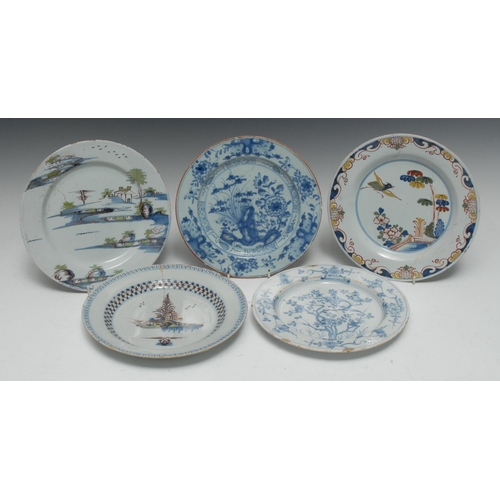 10C - An 18th century Delft circular plate, painted with a stylized Chinese landscape in tones of blue, gr...
