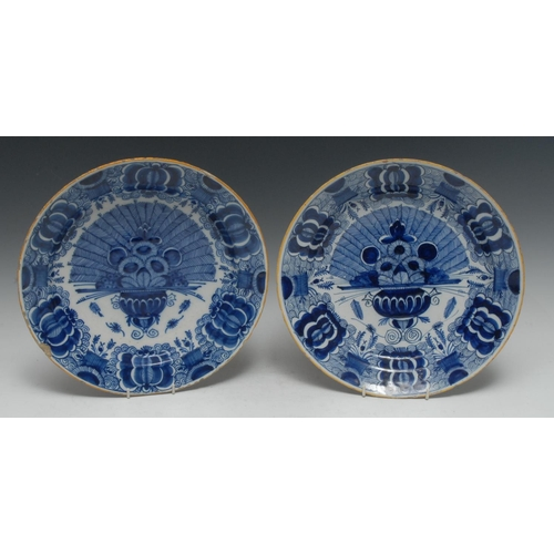 16 - An 18th century Delft dish, painted in tones of blue with a vase of flowers, yellow line border, 31....