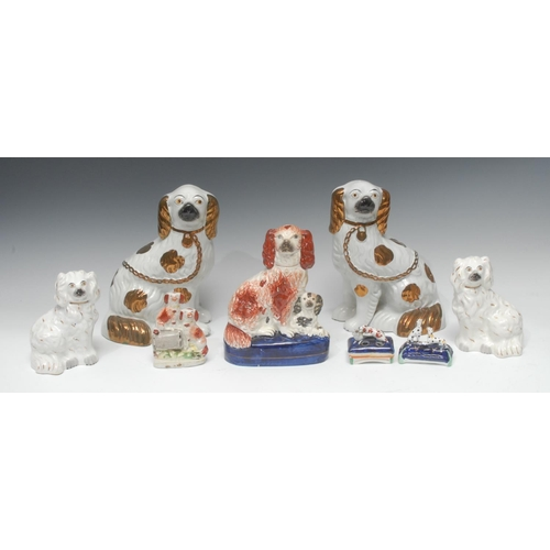 24 - A pair of Staffordshire dogs, seated to the left and right, front legs free,  copper lustre markings...