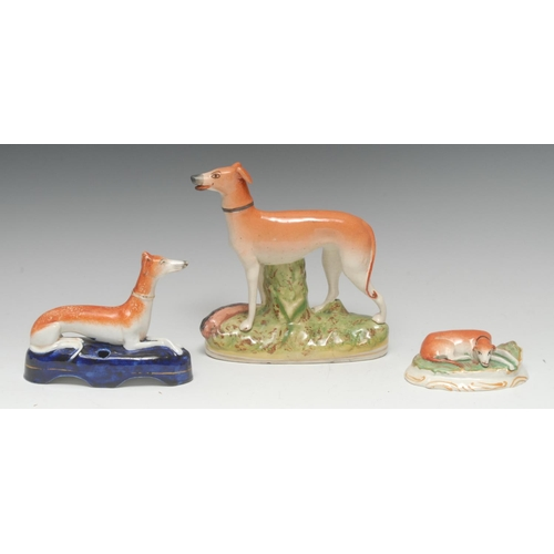 31 - A Staffordshire greyhound, tan markings, oval base, 18.5cm high, c.1870;  a similar pen holder, with...