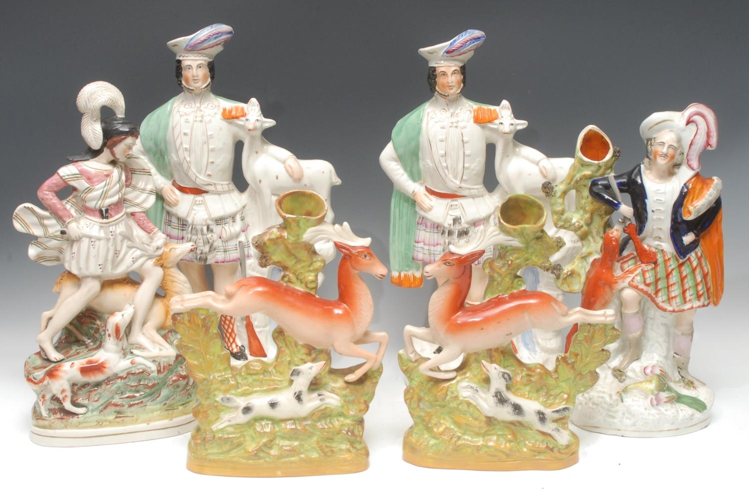 A pair of Victorian Staffordshire flatback spill vases, modelled as hounds...