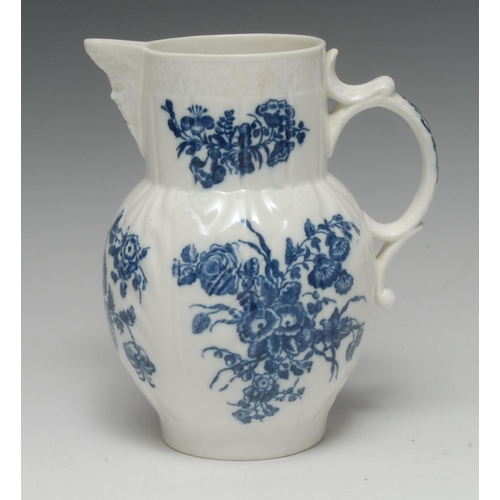 60 - A Caughley cabbage leaf moulded mask jug, printed in underglaze blue with flower sprays, C-scroll ha...