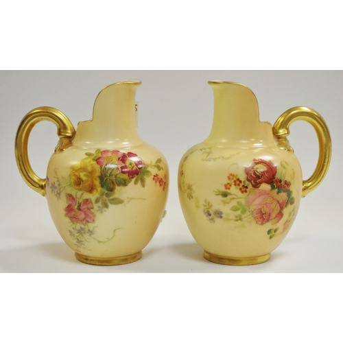 19 - A pair of Royal Worcester blush ivory globular jugs with ribbed gilt handles...