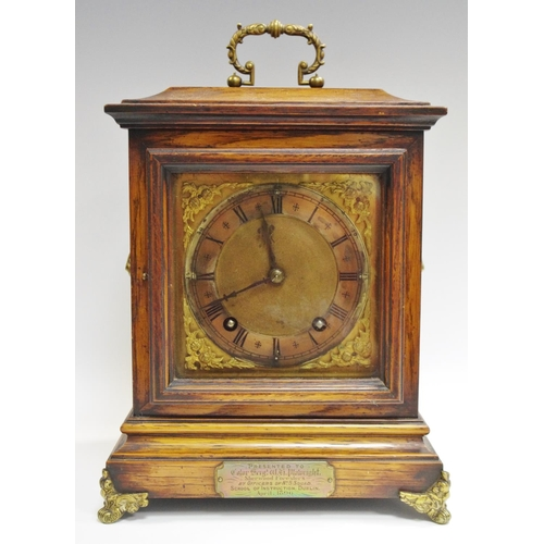 23 - A late Victorian oak mantel clock, with military interest plaque...
