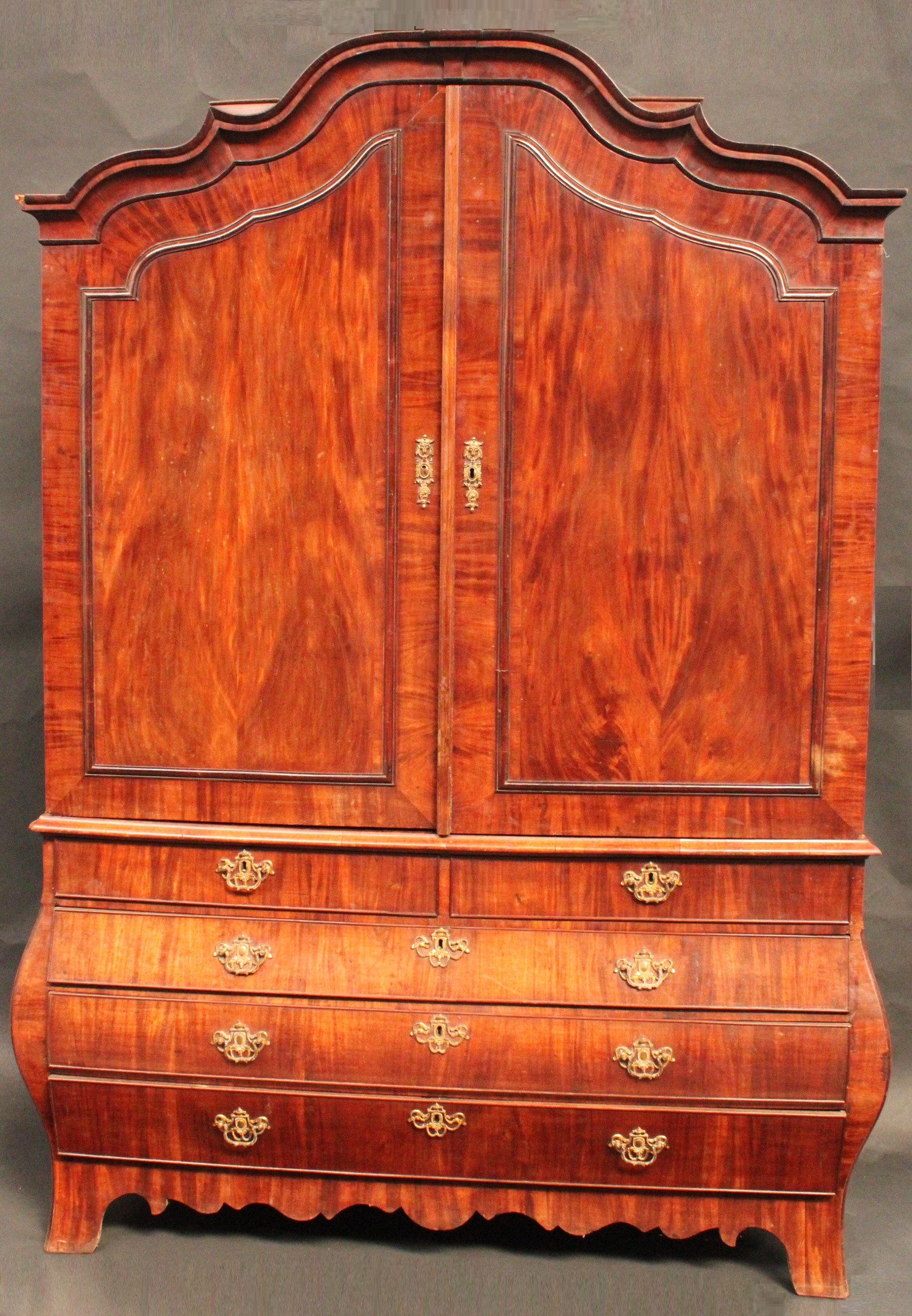 A large 19th century Dutch mahogany bombe shaped linen press, shaped arched...