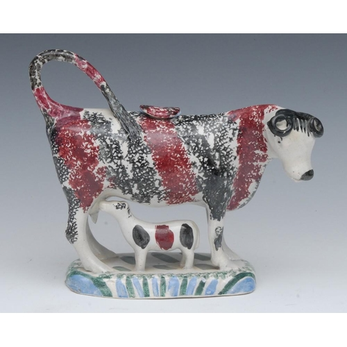 11 - A 19th century Pearlware cow creamer, possibly Yorkshire, standing four square, sponged in black and...
