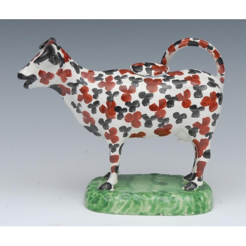25 - A North of England cow creamer, standing four square, with black and rust stylised leaf  patch marki...