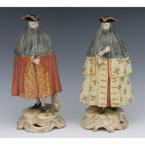 26 - A pair of Continental pottery figures, of carnival revellers, both standing wearing tricorn hats, la...