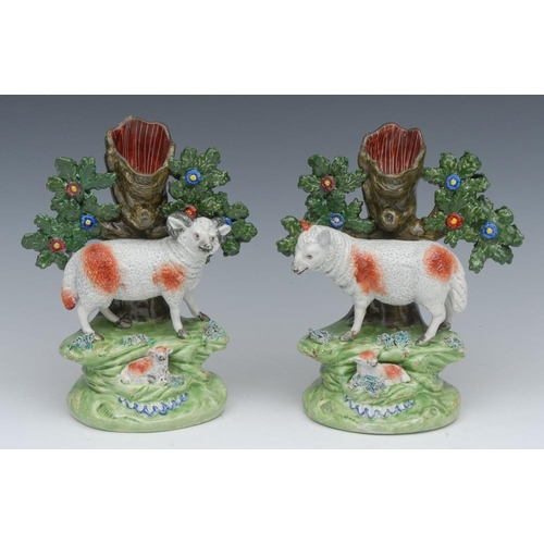 27 - A pair of John Walton spill vases, with ram and lamb and ewe and lamb before bocage, 18cm high, mark...