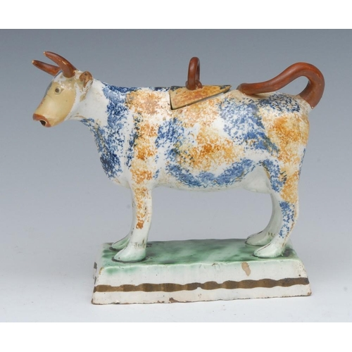 31 - A Prattware cow creamer and cover, standing four square, sponged in ochre and blue, brown horns and ...
