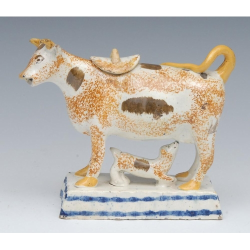 32 - A Prattware cow creamer and cover, standing four square, sponged in ochre, tan patch markings, yello...