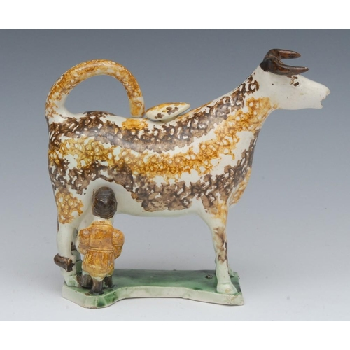 33 - A Prattware cow creamer and cover, standing four square, the back legs hobbled, the milkmaid seated ...