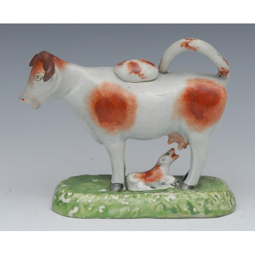 36 - A Staffordshire cow creamer, standing four square, with calf, rust patch markings, rounded rectangul...