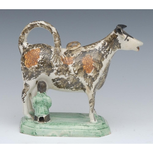 4 - A 19th century cow creamer and cover, standing four square, with milkmaid, sponged in black and roun...