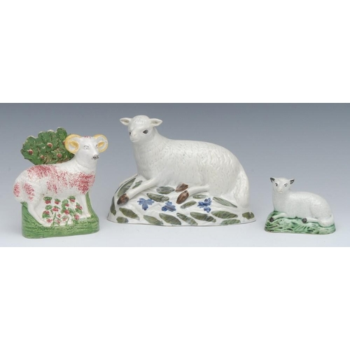 43 - An 18th century English  Pearlware lamb, recumbent, the base with stylised blue flowerheads and gree...