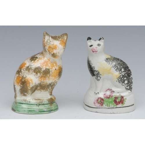 44 - An 18th century North of England cat, seated to the left, sponged in black and tan, green base, 8.75...