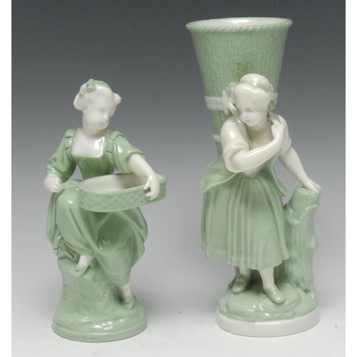58 - A Minton celadon figural spill vase, modelled as a rustic girl carrying a wicker basket, glazed in t...