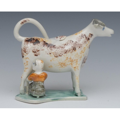 6 - A 19th century cow creamer and cover, standing four square, with milkmaid, sponged in ochre and tan,...