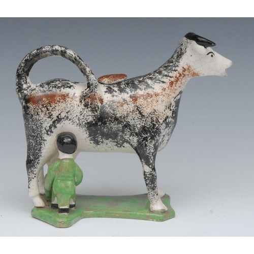 7 - A 19th century cow creamer and cover, standing four square, with milkmaid, sponged in ochre and blac...
